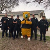 Officers stand with a mascot